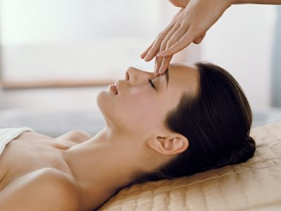 Side on shot of brown haird woman recieving facial with eyes closed to the forehead. Shot is of model's head and shoulders. spa treatment.